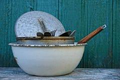 Uma pilha de pratos sujos em uma bacia cinzenta em uma tabela contra uma parede verde foto de stock royalty free