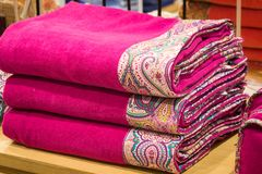 Uma pilha de toalhas brilhantes com ornamento originais textile Acessórios do banho fotografia de stock royalty free