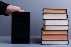 Uma pilha de vários livros e ao lado de alguém que guarda uma tabuleta O conceito da educação imagem de stock