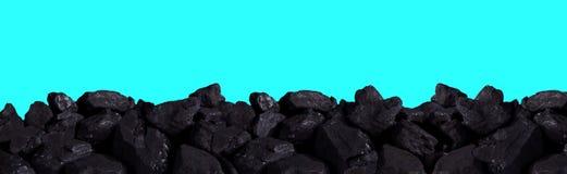 Uma pilha do carvão preto em um fundo do céu azul foto de stock
