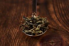 Uma pilha do chá verde em uma colher, em um fundo de madeira Close-up Foto de Stock