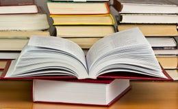 Uma pilha dos livros com a biblioteca na parte traseira Fotos de Stock