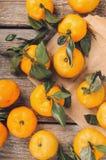 Uma pilha dos mandarino doces frescos com as folhas verdes na tabela de madeira no papel do ofício Vista superior, configuração l imagens de stock royalty free