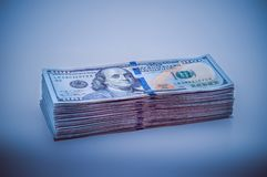 Uma pilha grande de contas de cem-dólar Projeto azul vignetting imagens de stock royalty free