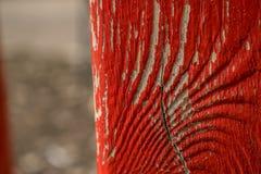 Uma pintura rachada velha da cor vermelha em uma superfície de madeira ondulada, que seja cruzada por uma quebra Fotos de Stock Royalty Free