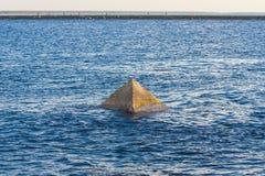 Uma pirâmide de pedra que projeta-se da água. Fotos de Stock Royalty Free