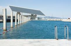 Uma piscina do seawater na frente de uma potência solar Fotos de Stock Royalty Free