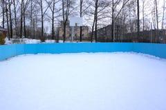 Uma pista exterior da patinagem no gelo e uma rede do hóquei com geada alta cobriram árvores no fundo em uma paisagem do inverno foto de stock royalty free