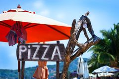 Uma pizza do sinal de anúncio na praia foto de stock