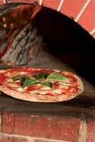 Uma pizza fresca fora de um forno Madeira-despedido do tijolo Imagens de Stock