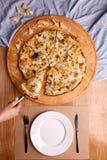 Uma pizza inteira é servida na tabela fotografia de stock royalty free