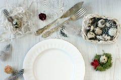 Uma placa branca limpa para comer na tabela, a preparação para a Páscoa, os ovos de codorniz e as penas em uma cesta, decorações Imagens de Stock Royalty Free