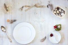 Uma placa branca limpa para comer na tabela, a preparação para a Páscoa, os ovos de codorniz e as penas em uma cesta, decorações Imagem de Stock Royalty Free