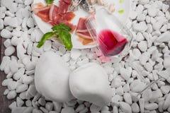 Uma placa com carne salgada, queijo, nozes e manjericão, um povo e uma faca em pedras de um branco e em um fundo de madeira Fotografia de Stock