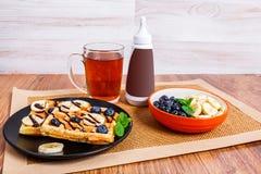 Uma placa com waffles belgas, molho de chocolate e uma caneca de chá imagens de stock