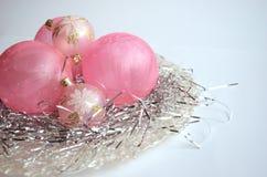 Uma placa da madrepérola com os ornamento cor-de-rosa geados da bola do Natal na decoração de prata do cabelo com espaço da cópia Imagens de Stock
