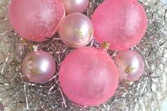 Uma placa da madrepérola com os ornamento cor-de-rosa geados da bola do Natal na decoração de prata do cabelo com espaço da cópia Imagem de Stock Royalty Free