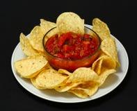 Uma placa das microplaquetas e da salsa fresca Fotografia de Stock