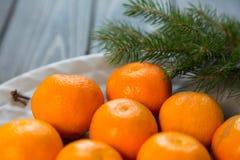 Uma placa das tangerinas fica na tabela de madeira foto de stock