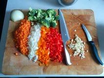 Uma placa de corte com as cebolas, pimentas, brócolis, as cenouras e as facas acima desbastados imagem de stock royalty free