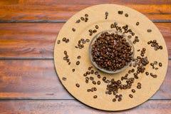 Uma placa de feijões de café inteiros em um fundo de madeira imagem de stock royalty free
