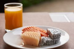 Uma placa de frutos do cantalupo, do quivi e da papaia na tabela fotos de stock