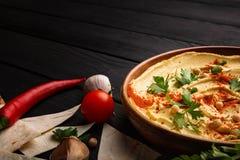 Uma placa de madeira do hummus com salsa, cereja da paprika, pimenta de pimentão vermelho em um fundo de madeira escuro foto de stock royalty free