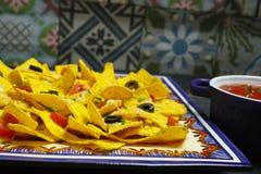 Uma placa de nachos deliciosos da tortilha com molho de queijo derretido, c Foto de Stock Royalty Free