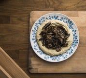Uma placa do hummus do cogumelo, fundo de madeira foto de stock