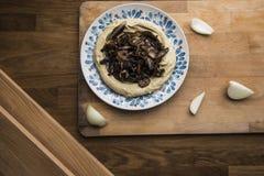 Uma placa do hummus do cogumelo, fundo de madeira imagens de stock royalty free