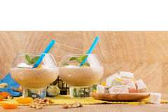 Uma placa do loukoum, dois vidros dos cocktail, nozes, abricós secados brilhantes em um fundo de madeira imagens de stock