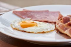 Uma placa do ovo frito, do bacon e do presunto deliciosos do estrelado imagens de stock