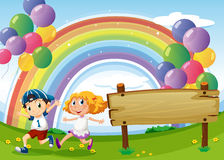 Uma placa vazia e duas crianças que jogam abaixo dos balões de flutuação Foto de Stock