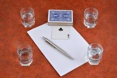 Uma plataforma de cartões de jogo, de pena, de papel e de pilhas de vodca no t Fotografia de Stock