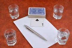 Uma plataforma de cartões de jogo, de pena, de papel e de pilhas de vodca no t Foto de Stock Royalty Free