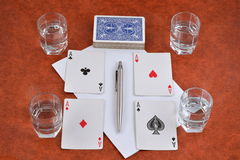 Uma plataforma de cartões de jogo, de pena, de papel e de pilhas de vodca no t Fotos de Stock Royalty Free