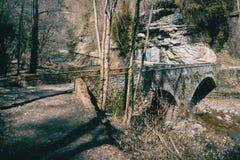 Uma ponte antiga que cruza um rio fotografia de stock royalty free