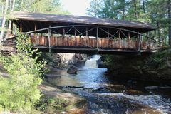 Uma ponte coberta com uma cachoeira embaixo Fotos de Stock