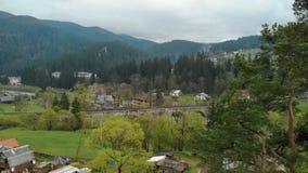 Uma ponte de estrada de ferro de pedra antiga sobre um rio defluxo e uma estrada entre as montanhas em uma vila pequena video estoque