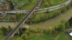 Uma ponte de estrada de ferro de pedra antiga sobre um rio defluxo e uma estrada entre as montanhas em uma vila pequena filme