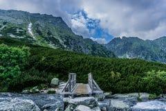 Uma ponte de madeira da montanha sobre o rio imagens de stock