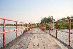 Uma ponte de madeira do pé através de uma via navegável fotografia de stock