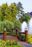Uma ponte de madeira moderna através do lago com as fontes, cercadas por árvores verdes altas com uma casa de campo e um azul Imagens de Stock