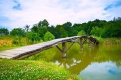 Uma ponte de madeira pequena através de um rio imagem de stock