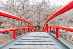Uma ponte vermelha em Ikaho Onsen no outono é um locat da cidade da mola quente fotografia de stock