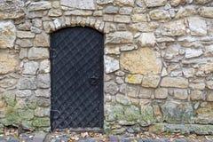 Uma porta antiga no preto com uma grande textura da estrutura com grandes rebites na perspectiva de uma parede e de um st não-des foto de stock