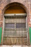 Uma porta arqueada velha em uma construção de tijolo foto de stock