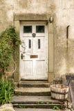 Uma porta branca velha com uma cubeta de madeira foto de stock