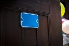 Uma porta da rua aberta com uma placa azul, um fundo dos balões e um humor festivo uma porta velha marrom e um fundo colorido bal Foto de Stock Royalty Free