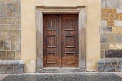 Uma porta dobro de madeira com quadro de porta do retângulo em uma parede de pedra imagens de stock